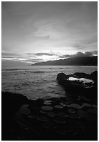Water-filled  grinding stones holes (foaga) and Leone Bay at sunset. Tutuila, American Samoa ( black and white)