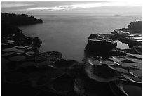 Ancient grinding stones (foaga) and Leone Bay at dusk. Tutuila, American Samoa ( black and white)