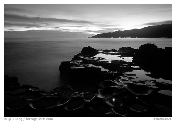 Grinding stones holes (foaga) filled with water at dusk, Leone Bay. Tutuila, American Samoa (black and white)