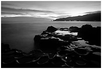 Grinding stones holes (foaga) filled with water at dusk, Leone Bay. Tutuila, American Samoa ( black and white)