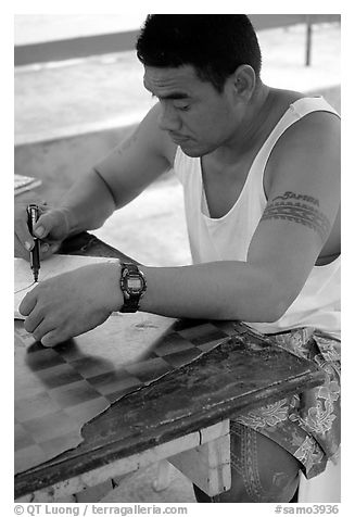 Young man drawing an artwork based on traditional siapo designs. Pago Pago, Tutuila, American Samoa (black and white)