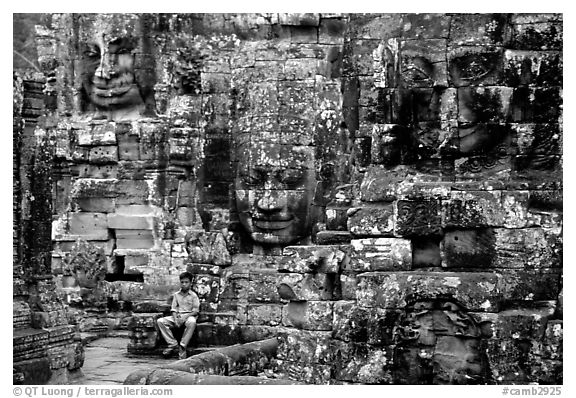 Boy sits next to large stone smiling faces, the Bayon. Angkor, Cambodia (black and white)