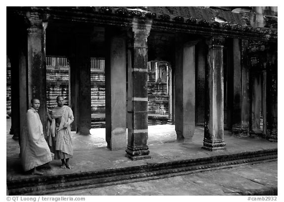 Two Buddhist monks in dark temple, Angkor Wat. Angkor, Cambodia (black and white)