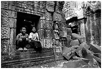 Boy and girl sit at window in Ta Prom. Angkor, Cambodia (black and white)