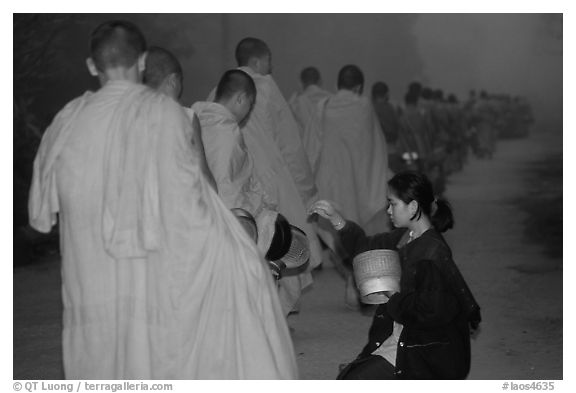 Woman gives alm during morning procession of buddhist monks. Luang Prabang, Laos (black and white)