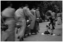 Buddhist monks walking past alm-giving woman. Luang Prabang, Laos (black and white)