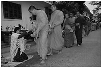 Buddhist monks receiving alm from woman. Luang Prabang, Laos (black and white)