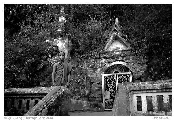 Novice Buddhist monk at entrance of cave, Pak Ou. Laos (black and white)