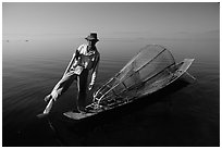 Intha fisherman on duggout with net. Inle Lake, Myanmar (black and white)