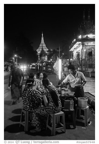 Women eating at street stall at night with Shwedagon Pagoda in background. Yangon, Myanmar (black and white)