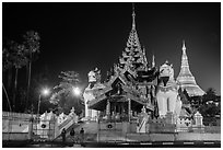 Southern gate guarded by two leogryphs and Main Stupa at night, Shwedagon Pagoda. Yangon, Myanmar ( black and white)