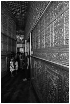 Worshippers inside maze-like walkway lined with glass showcases, Botataung Pagoda. Yangon, Myanmar ( black and white)