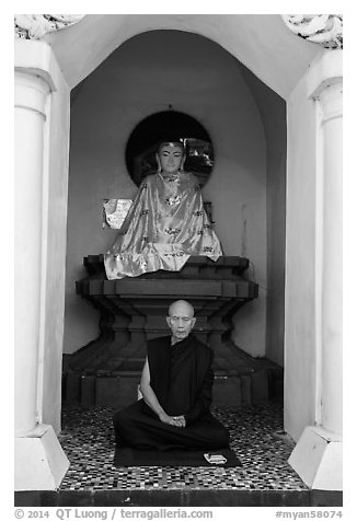 Monk meditating in alcove with Buddha statue, Shwedagon Pagoda. Yangon, Myanmar (black and white)