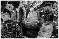 Woman and monk in pavillion surrounded by Buddha statues. Yangon, Myanmar ( black and white)