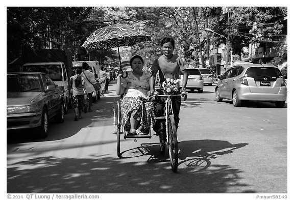 Woman holding unbrella against sun while riding Trishaw. Yangon, Myanmar (black and white)