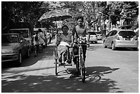 Woman holding unbrella against sun while riding Trishaw. Yangon, Myanmar ( black and white)