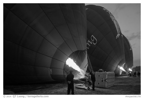 Crew inflates hot air balloons with propane burners. Bagan, Myanmar (black and white)