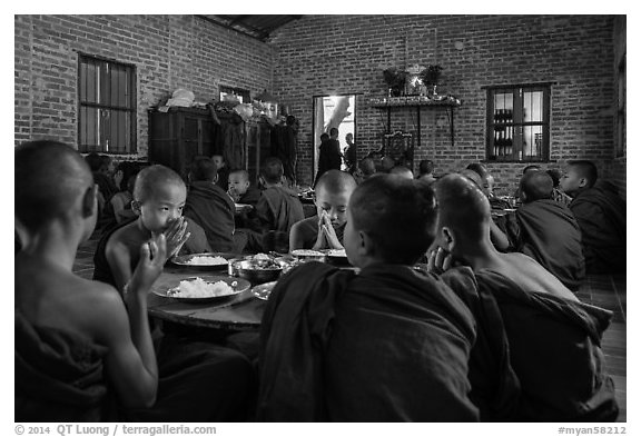 Buddhist novices pray at table before eating lunch, Nyaung U. Bagan, Myanmar (black and white)