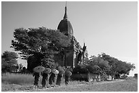 Five novices with red umbrellas walking below temple. Bagan, Myanmar ( black and white)