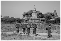 Buddhist Novices with red sun umbrellas on path near old stupas. Bagan, Myanmar ( black and white)