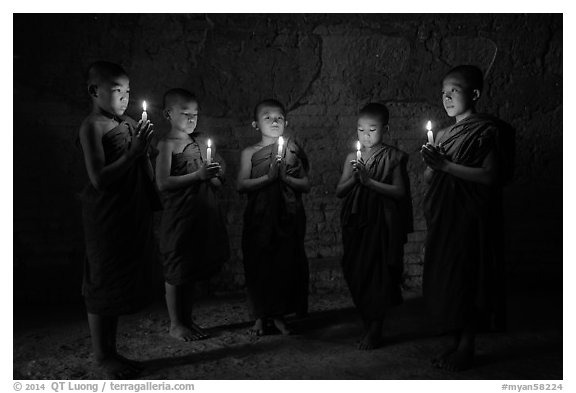 Five novices standing in circle inside temple with candles. Bagan, Myanmar (black and white)