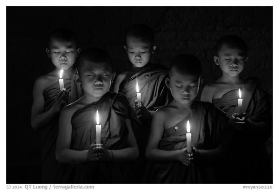 Young buddhist monks holding candles with eyes closed. Bagan, Myanmar (black and white)