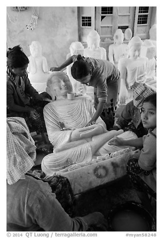 Women polishing buddha statue. Mandalay, Myanmar (black and white)