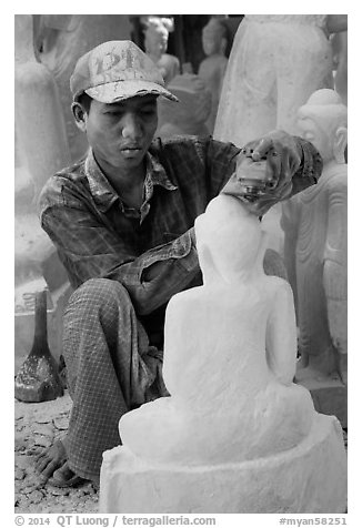 Sculptor carving buddha statue out of a block of white marble. Mandalay, Myanmar (black and white)
