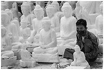 Man working amongst many  buddha statues on Marble street workshop. Mandalay, Myanmar ( black and white)