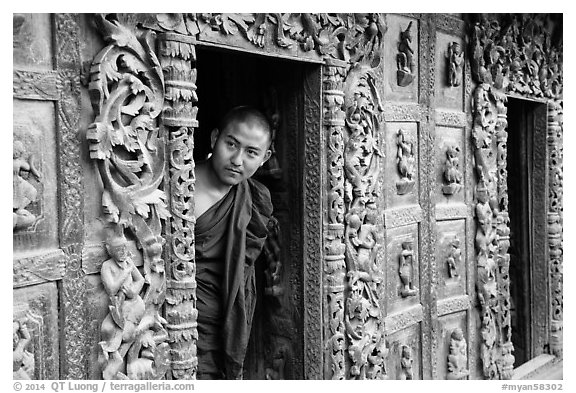 Exquisitely carved teak walls and monk pearing, Shwe In Bin Kyaung pagoda. Mandalay, Myanmar (black and white)