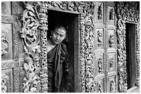 Exquisitely carved teak walls and monk pearing, Shwe In Bin Kyaung pagoda. Mandalay, Myanmar ( black and white)