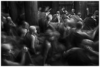 Monks in motion during prayer. Mandalay, Myanmar ( black and white)