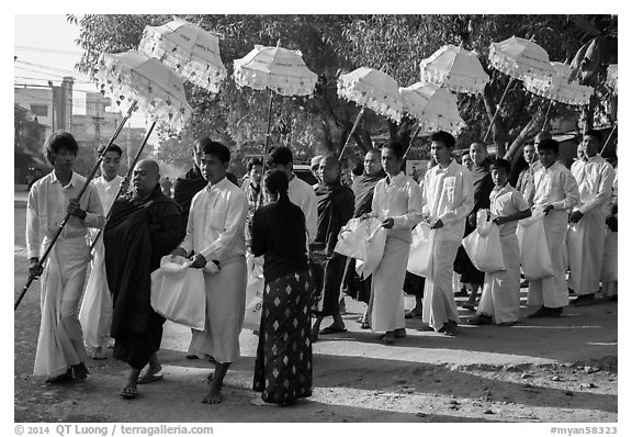 Umbrella bearer, Monks, and donation holders in alms procession. Mandalay, Myanmar (black and white)