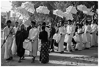 Umbrella bearer, Monks, and donation holders in alms procession. Mandalay, Myanmar ( black and white)