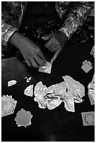 Close-up of hands separating gold leaves. Mandalay, Myanmar ( black and white)