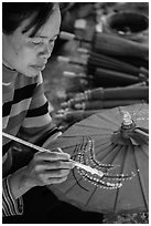 Woman painting the paper sun umbrellas carried by the monks. Pindaya, Myanmar ( black and white)