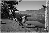 Man carrying baskets on road near Pone Tanoke Lake. Pindaya, Myanmar ( black and white)