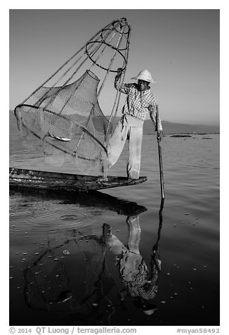 Intha fisherman with freshly caught fish in basket. Inle Lake, Myanmar (black and white)