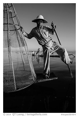 Intha fisherman prepares to release conical basket. Inle Lake, Myanmar (black and white)