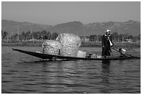 Man transporting baskets on boat. Inle Lake, Myanmar ( black and white)