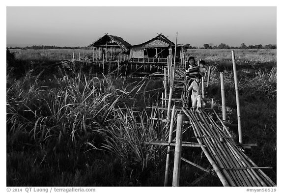 Family walking out of stilt house on precarious bridge. Inle Lake, Myanmar (black and white)
