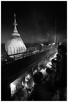 Pilgrims light up candles behind the Golden Rock at dusk. Kyaiktiyo, Myanmar ( black and white)