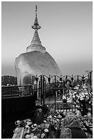 Pilgrim and food offerings behind Golden Rock at dawn. Kyaiktiyo, Myanmar ( black and white)