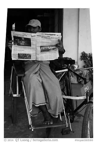 Cyclo driver reading newspaper with picture of QT Luong tour group. Bago, Myanmar (black and white)