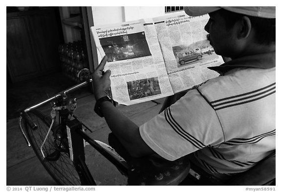 Cyclo driver looking at picture of QT Luong tour group in newspaper. Bago, Myanmar (black and white)