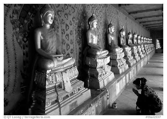 Woman worships a buddha image, Wat Arun. Bangkok, Thailand (black and white)