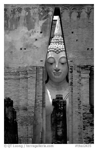 Monumental Buddha image seen between walls,  Wat Si Chum. Sukothai, Thailand (black and white)