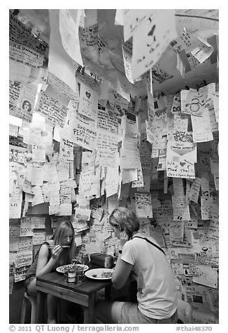 Women eating at Pad Thai restaurant decorated with customer notes, Ko Phi-Phi Don. Krabi Province, Thailand (black and white)