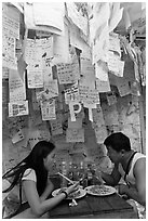 Couple eating Pad Thai below notes of praise left by customers, Ko Phi Phi. Krabi Province, Thailand ( black and white)