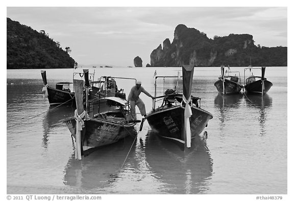 Man stepping on boats, Ao Lo Dalam, Ko Phi-Phi Don. Krabi Province, Thailand (black and white)